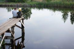 Bracia łowi na brzeg rzeki Dzieciaki jest usytuowanym z kijami w rękach Fotografia Royalty Free