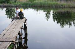 Bracia łowi na brzeg rzeki Dzieciaki jest usytuowanym z kijami w rękach Obraz Royalty Free