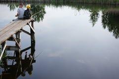 Bracia łowi na brzeg rzeki Dzieciaki jest usytuowanym z kijami w rękach Obrazy Royalty Free