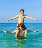 Bracia cieszy się jasnego grżą wody i sztuki piggyback Zdjęcia Royalty Free