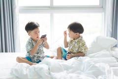 Bracia słuchają piosenkę z telefonem komórkowym w ranku na łóżku fotografia royalty free