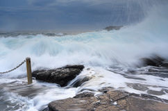 Bracing as powerful waves come crashing over rocks Stock Photography