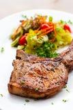Braciola di maiale con la fine dell'insalata su fotografie stock libere da diritti