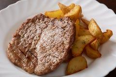 Braciola di maiale deliziosa e cunei della patata, primo piano Fotografia Stock