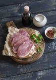 Braciole e spezie di maiale crude su un tagliere di legno rustico Fotografia Stock Libera da Diritti