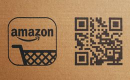 Amazon Company Shopping Trolley Logo and QR Code on Cardboard. Bracknell, England - February 10, 2018: Close up of the Amazon company shopping trolley logo next Royalty Free Stock Images