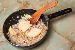 Bradende ui. Voeg boter in fijngehakte ui toe. Stock Afbeelding