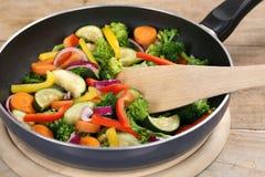Bradende voedselgroenten in het koken van pan met spatel Royalty-vrije Stock Afbeeldingen