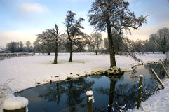 Bradenham Lane Marlow. View across snow covered fields with seream and tree reflected in surface Royalty Free Stock Photography