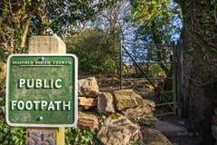BRADFIELD UK - 16TH FEBRUARI 2019: Ett fyrkantigt grönt offentligt vandringsledtecken framme av en metallport fotografering för bildbyråer