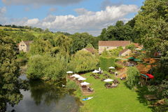 Bradford on Avon, UK - AUGUST 12, 2017: People relaxing in a Pub Garden beside the river Avon in Avoncliff picture taken from Avo Stock Photography