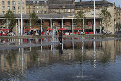 Bradford Centenary Square. And town hall, in West Yorkshire, England, with area of water fountains in the foreground and a man walking across the water Royalty Free Stock Photography