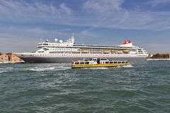 Braemar cruise ship and water bus in Venice lagoon, Italy. MS Braemar luxury cruise ship and water bus or vaporetto in Venice lagoon. Venice is situated across Stock Photo