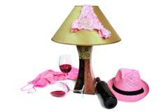 Bragas en la lámpara cerca de la botella de vino y de dos vidrios Foto de archivo libre de regalías