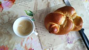 Braid bread and coffee breakfast. Breakfast ready on a table, mug of coffee and braid bread with knife Stock Image