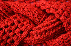 Braid crochet fabric texture. Braided red crocheted yarn textured fabric with puff stitches, front-post and back-post stitches Royalty Free Stock Photo
