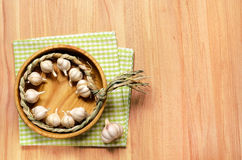 Braid of garlic on wooden table. Royalty Free Stock Images