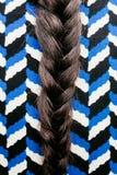 Braid on a herringbone pattern drees. Braid on a herringbone pattern dress in the street detail. Back view Stock Photography