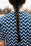 Braid on a herringbone pattern drees. Young woman with braid and herringbone pattern dress in the street. Back view Royalty Free Stock Photography