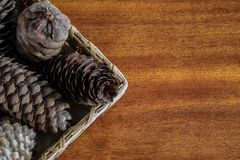 Basket of cones. A braided basket with spruce and pine cones on wooden table Stock Photography