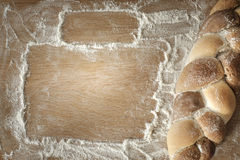 Braided bread lies on a wooden table with flour Royalty Free Stock Images