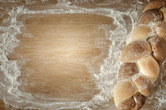 Braided bread lies on a wooden table with flour Stock Photo