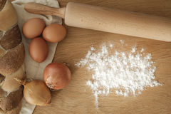 Braided bread with onions, eggs, flour and a rolling pin on a wo Stock Photo