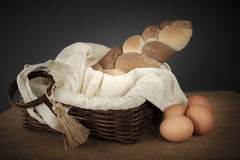 Braided bread in a wicker basket and eggs on the table Stock Photos