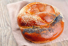 Braided bun, sprinkled with poppy seeds and sesame seeds on a ol Royalty Free Stock Photography