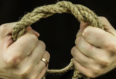 Braided coconut rope in the hands of men in tension squeezing. Black background Royalty Free Stock Images