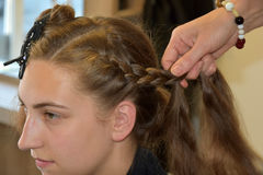 Braided hair. Young girl with long blond hair at the hairdresser, she gets a new hairstyle, braided hair round the head Stock Photo