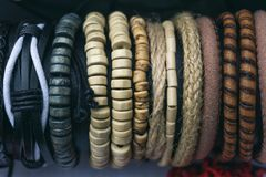 Braided handmade leather and wooden bracelets background. Braided handmade leather and wooden bracelets stock images