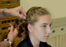 Braided hair. Young girl with long blond hair at the hairdresser, she gets a new hairstyle, braided hair round the head Stock Image