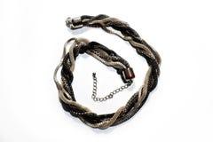 Braided metallic snake necklace on white background stock photos
