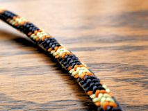 Braided Nylon Rope Knot on Wood Grain Background for Climbing, Camping Royalty Free Stock Photos