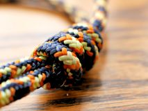 Braided Nylon Rope Knot on Wood Grain Background for Climbing, Camping Stock Photos
