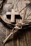 Braided palm, cross and crown of thorns. Closeup of a small traditional spanish braided palm to be blessed on Palm Sunday, a small wooden cross and a depiction Stock Photo