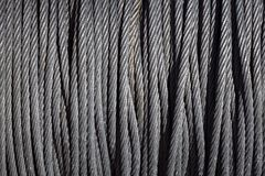 Braided steel seam rope wound in a bay. The texture of a braided sea rope. Cean new steel cable steel wire or steel rope, rope sling drum Royalty Free Stock Photography