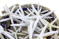 Braided straw basket full of starfish, isolated on white. Royalty Free Stock Photos