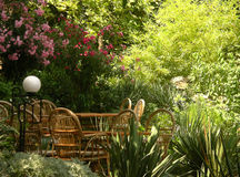 Braided tables and chairs in the garden. Wooden braided tables and chairs in the beautiful garden Royalty Free Stock Photography