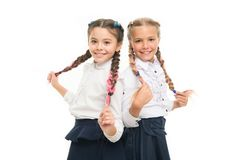 Braiding hair. Adorable little girls with plaited hair isolated on white. Cute small children holding long hair braids. Wearing school uniform. Luxurious hair stock images