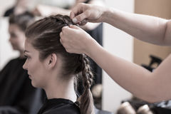 Braiding young woman's hair Stock Images