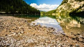 Braies与大岩石的湖视图在前景 免版税图库摄影
