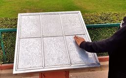Braille alphabet with Braille numbers. For the blind persons on metallic background installed in Taj Mahal complex in Agra. One unidentified hand is reading the stock images