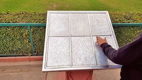 Braille alphabet with Braille numbers. For the blind persons on metallic background installed in Taj Mahal complex in Agra. One unidentified hand is reading the royalty free stock image