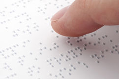 Braille reading. Close up of male hand reading braille text stock photo