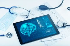 Diagnostics on tablet with brain functionality concept. Brain functionality report with medical devices around royalty free stock images