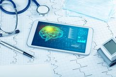 Diagnostics on tablet with brain functionality concept. Brain functionality report with medical devices around stock images
