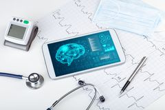 Diagnostics on tablet with brain functionality concept. Brain functionality report with medical devices aroundn royalty free stock photography