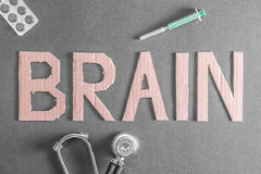Brain health. A stethoscope, pills and a disposable syringe on a dark background with the word brain made out of cardboard for your concepts about brain Royalty Free Stock Image